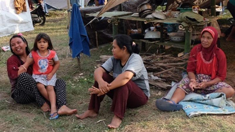 Indonesische mensen zitten op grond voor provisorische tent