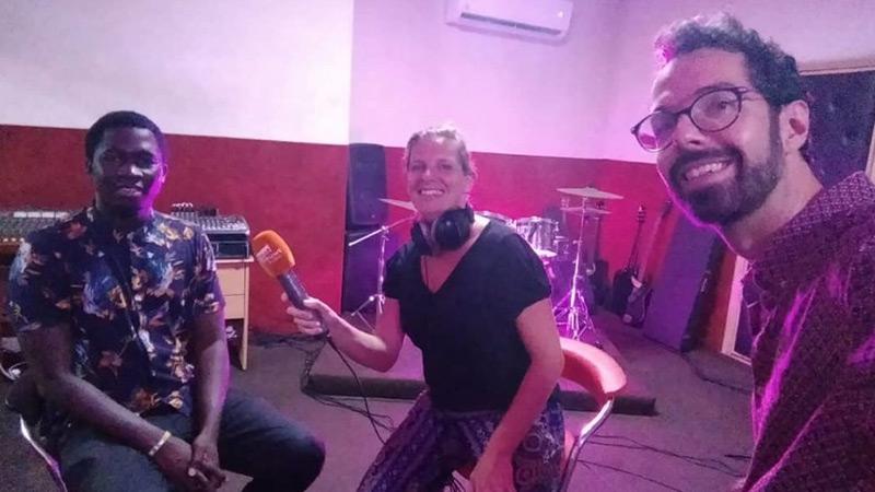 Presentatrice Annemarie met oranje microfoon in studio met zanger Cissa en zendeling Jan
