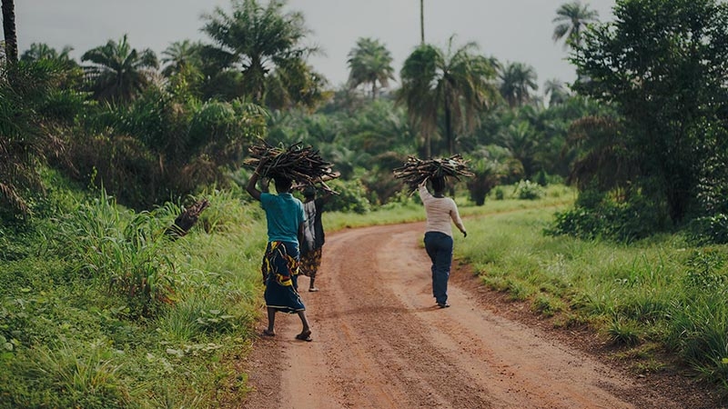 Afrikaanse vrouwen lopen op onverharde weg