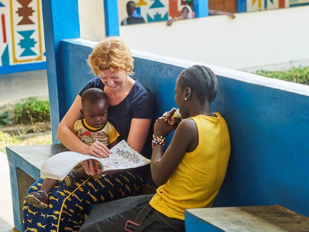 Zendeling Agaath samen met twee kinderen uit Guinee voor blauwe muur zittend