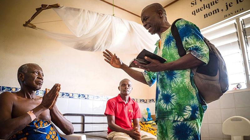 Voorganger uit Guinee in typische kleding bidt voor mensen in ziekenhuis