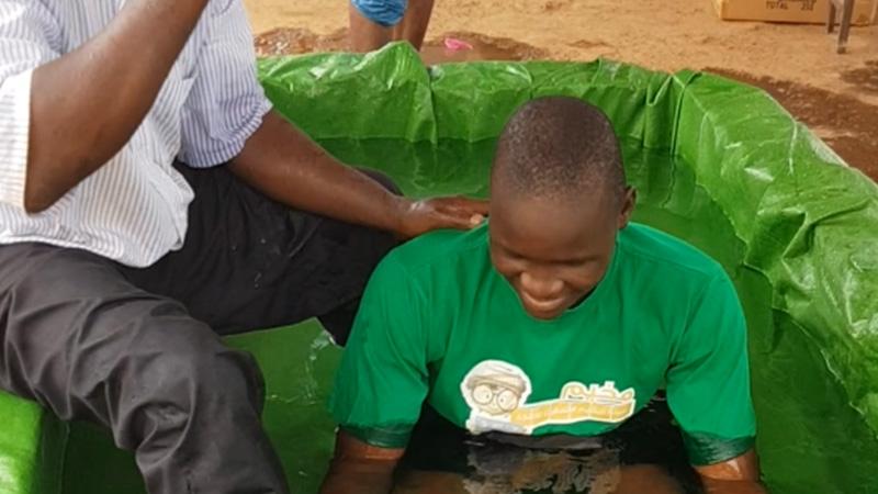 Jongen wordt gedoopt in zelfgemaakt doopbad met groen doek in gevangenis Guinee