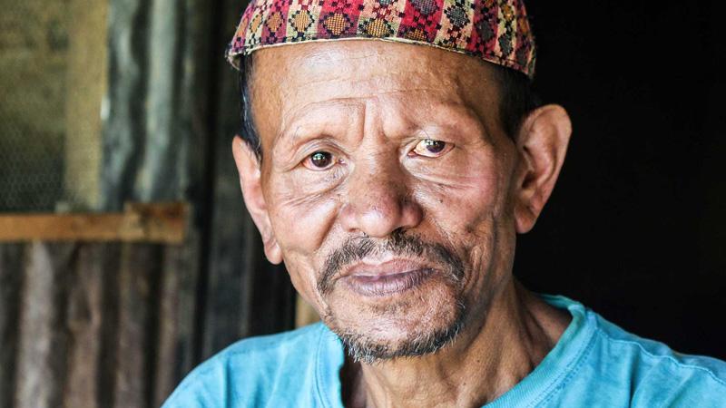 Aziatische man kijkt intens in de camera met snor en blauw t-shirt