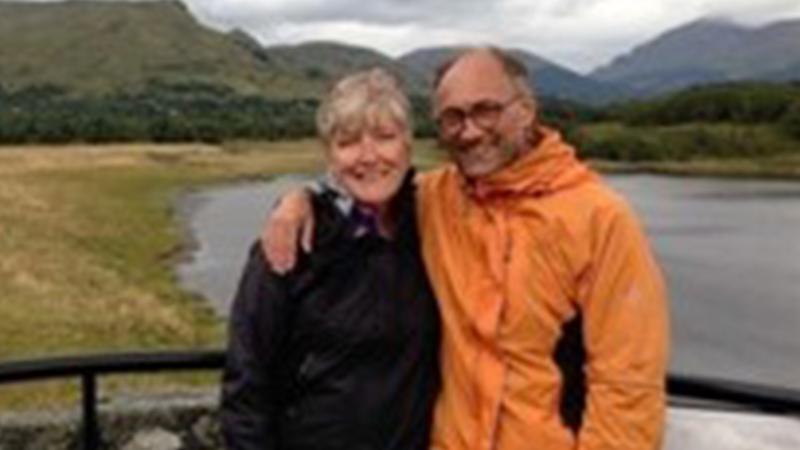 Oud zendeling Joke staat gearmd naast partner met natuur op achtergrond
