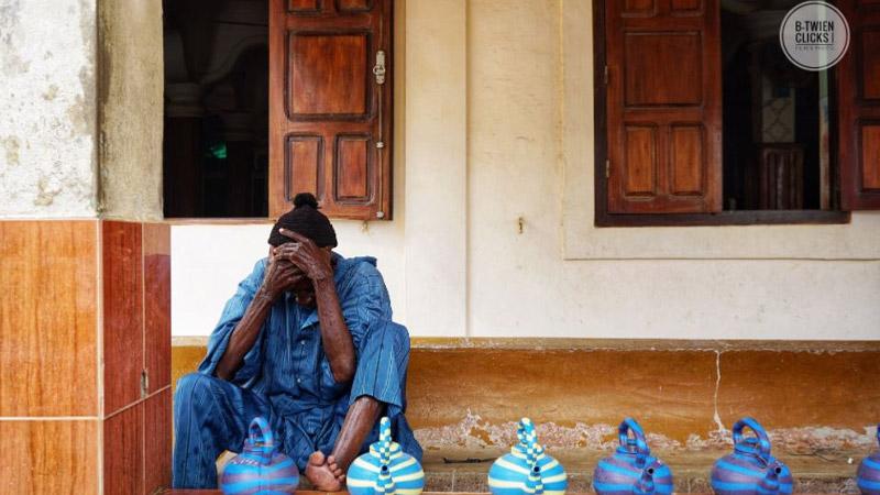 Vrouw in Senegal zit op grond met blauwe potten voor zich