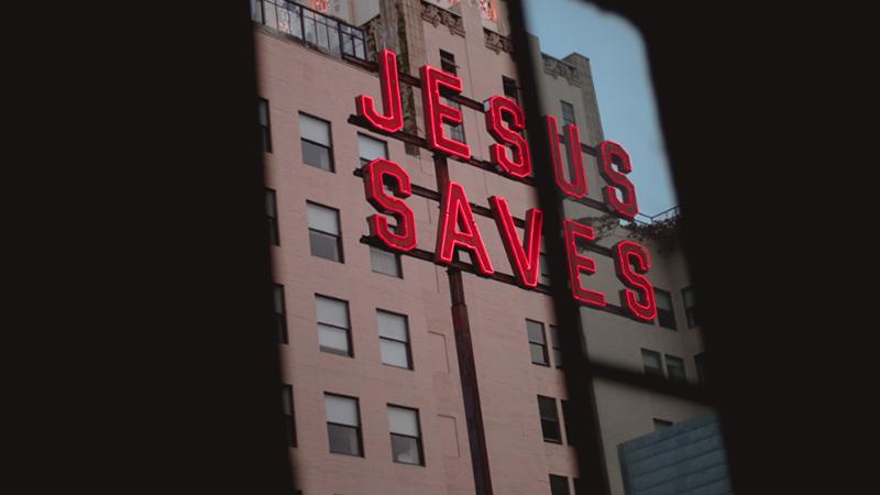 Flatgebouw met rood bord Jesus Saves