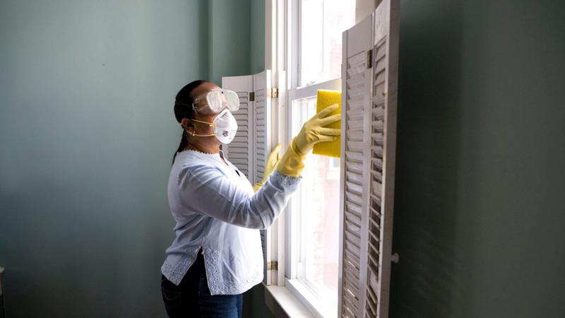Zendeling schoonmaakster maakt schoon met mondmasker en gele handschoenen