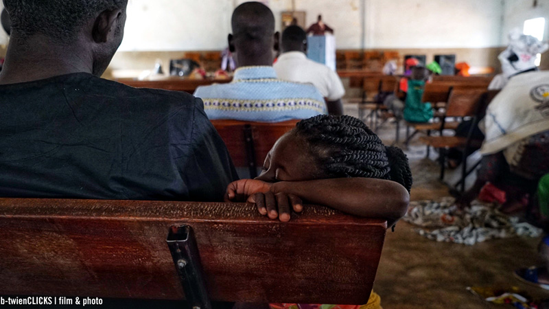 Afrikaanse kerk met jong kind wat in slaap gevallen is in kerkdienst