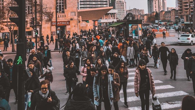 Mensenmassa steekt de straat over op zebrapad
