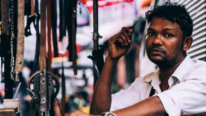 Man uit Myanmar kijkt in camera in drukke straat