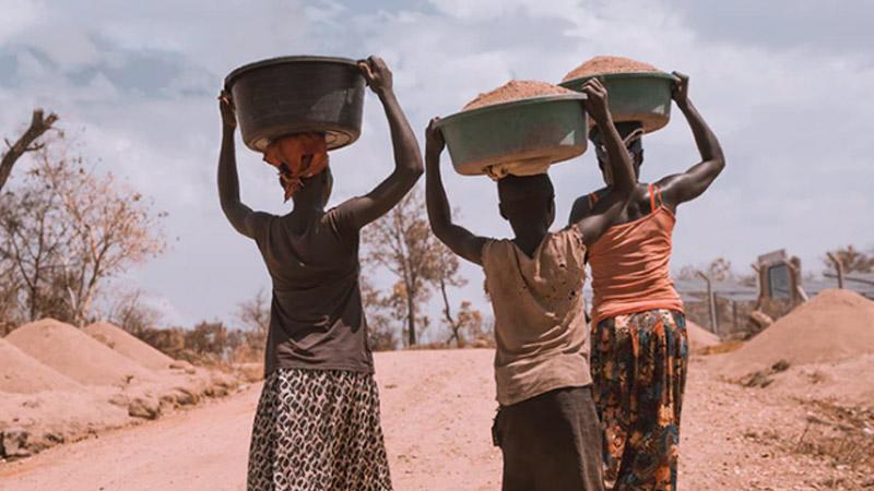 Afrikaanse vrouwen met zware manden op hun hoofd