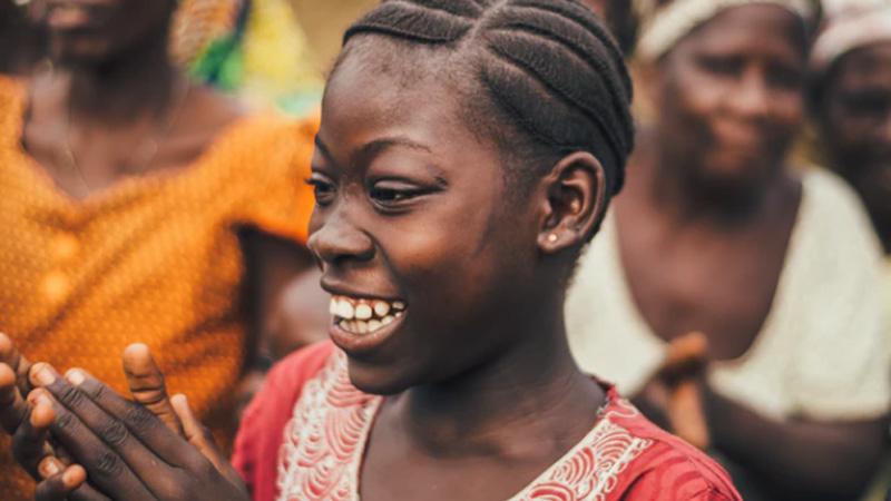 Jonge Afrikaanse vrouw in publiek lacht