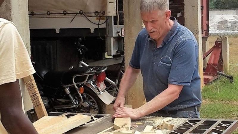 Zendeling op zendingsveld aan het werk met hout