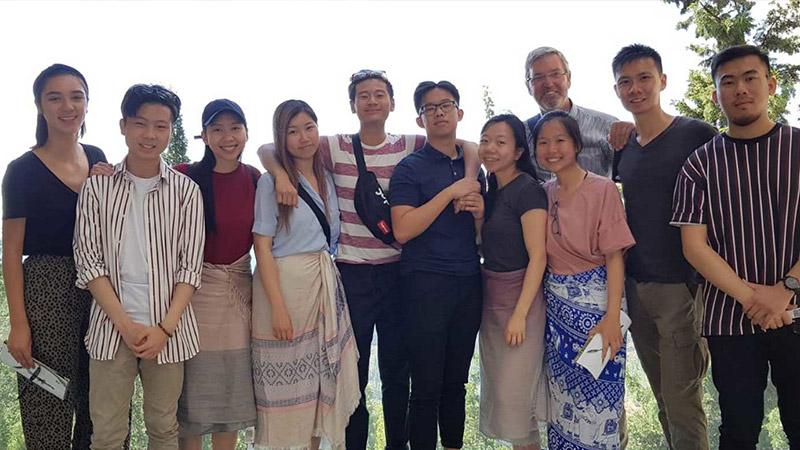 Groep jongeren staat in rijtje naast elkaar samen met reisbegeleider Hans