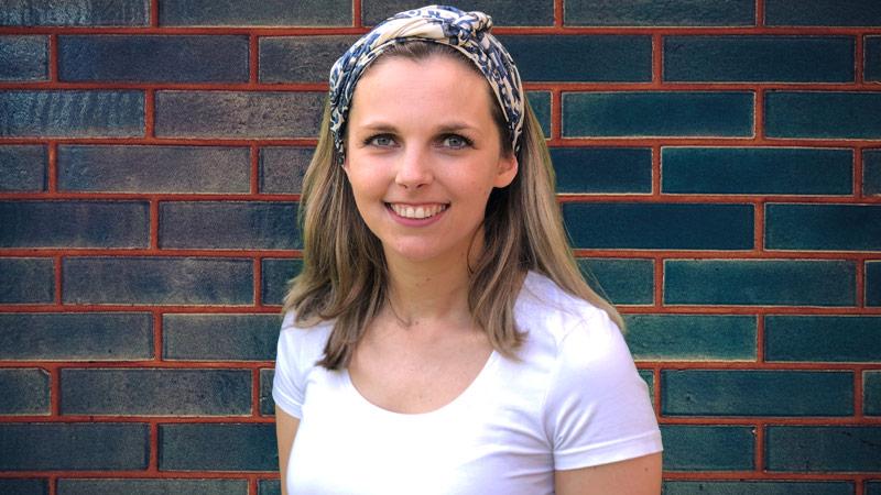 Rebecca met wit t-shirt en hoofddoek voor muur