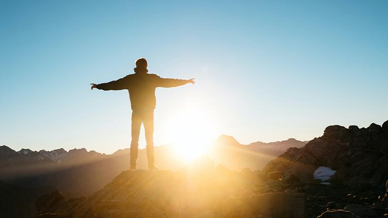 Man met open armen is aan het bidden